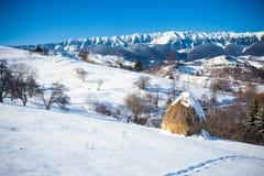 Vista scenica di inverno tipico con i mucchi di fieno Fotografie Stock Libere da Diritti