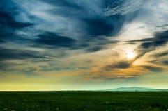 Vista scenica di un prato contro il cielo nuvoloso nel tramonto immagine stock libera da diritti