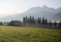 Vista scenica di una valle meravigliosa con la costruzione di casa rurale dell'azienda agricola con le montagne su fondo alla mat Immagini Stock