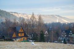 Vista scenica di una valle meravigliosa nelle montagne con le costruzioni di casa rurali dell'azienda agricola Fotografia Stock Libera da Diritti