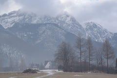 Vista scenica di una valle meravigliosa nelle montagne con le costruzioni di casa rurali dell'azienda agricola Fotografia Stock