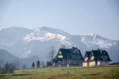 Vista scenica di una valle meravigliosa nelle montagne con le costruzioni di casa rurali dell'azienda agricola Fotografie Stock Libere da Diritti