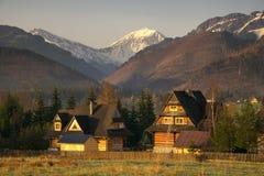 Vista scenica di una valle meravigliosa nelle montagne con le costruzioni di casa rurali di legno dell'azienda agricola Immagine Stock