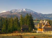 Vista scenica di una valle meravigliosa nelle montagne con le costruzioni di casa rurali di legno dell'azienda agricola Fotografia Stock Libera da Diritti