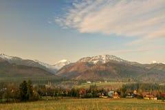 Vista scenica di una valle meravigliosa nelle montagne con le costruzioni di casa rurali di legno dell'azienda agricola Fotografia Stock