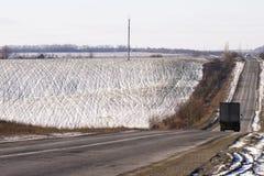 Vista scenica sulla strada asfaltata bagnata in tempo della neve di autunno con Immagine Stock Libera da Diritti