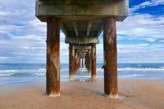 Vista sob um cais do oceano com o céu azul nebuloso imagem de stock royalty free