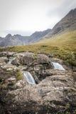 Vista sobre as rochas das cachoeiras para o Cullins das associações feericamente em Skye imagens de stock royalty free