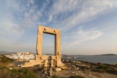 Vista sobre a cidade velha de Naxos durante todo as ruínas do monumento de mármore antigo Portara da entrada no por do sol, Gréci Foto de Stock Royalty Free