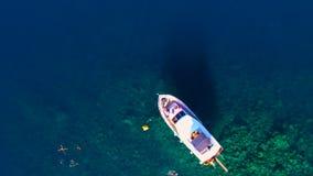 A vista sobre o iate privado no mar, pessoa banha-se perto do iate filme