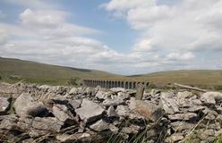 Vista sobre uma parede de pedra seca ao viaduto de Ribblehead nos vales de Yorkshire fotos de stock