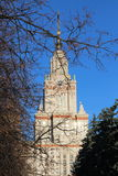 Vista soleada del edificio principal de la universidad de estado de Moscú con reflexiones en ventanas a través de ramas de árbol  Imágenes de archivo libres de regalías