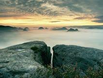 Vista sopra il bordo tagliente dell'arenaria nella valle lunga in pieno di prima foschia autunnale la valle nebbiosa della forest Fotografia Stock Libera da Diritti