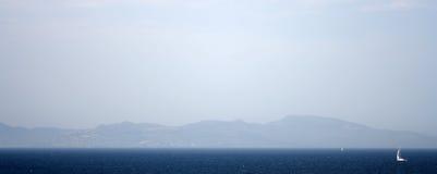 Vista sopra il mare blu e le montagne blu Fotografia Stock