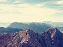 Vista sopra la scogliera e la valle alpine Sun all'orizzonte, cielo blu con poche nuvole Montagne delle alpi Immagini Stock