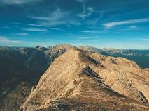 Vista sopra la scogliera e la valle alpine Sun all'orizzonte, cielo blu con poche nuvole Montagne delle alpi Immagine Stock