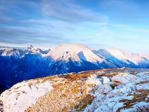 Vista sopra la scogliera e la valle alpine Sun all'orizzonte, cielo blu con poche nuvole Montagne delle alpi Fotografia Stock