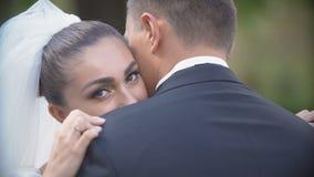 Vista sopra la spalla dello sposo alla bella sposa castana affascinante che sorride e che abbraccia tenero il suo amante all'aper stock footage