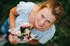 Vista sopraelevata del mazzo della tenuta della ragazza del redhair dei fiori e dello SMI Fotografia Stock Libera da Diritti