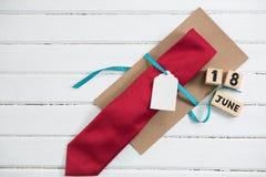 Vista sopraelevata del regalo della cravatta dal calendario sulla tavola Immagini Stock