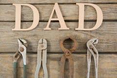 Vista sopraelevata del testo del papà dagli strumenti del lavoro sulla tavola Fotografia Stock
