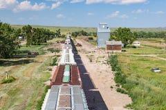 Vista sopraelevata del treno che passa il vecchio elevatore di grano Immagini Stock Libere da Diritti