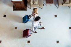 vista sopraelevata delle coppie dei viaggiatori che camminano con i bagagli immagini stock libere da diritti