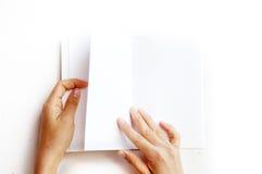 Vista sopraelevata delle mani che tengono un libro in bianco fotografie stock