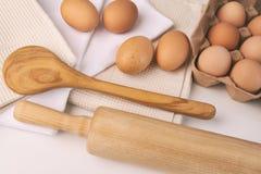 Vista sopraelevata delle uova, degli asciugamani e degli strumenti della cucina sulla tavola Fotografia Stock