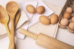 Vista sopraelevata delle uova e degli strumenti della cucina sulla tavola Fotografie Stock