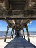 Vista sotto il molo di legno dell'oceano Immagine Stock