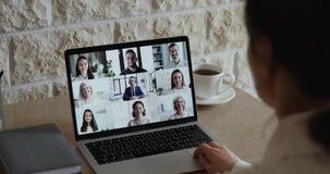 Vista a spalla dei dipendenti che comunicano con il team via webcam stock footage