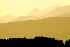 Vista spettacolare delle siluette della montagna Luce solare gialla nel primo mattino Immagini Stock Libere da Diritti
