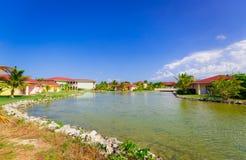 Vista splendida dei motivi e delle costruzioni della località di soggiorno in giardino tropicale contro il fondo del cielo blu Fotografie Stock Libere da Diritti