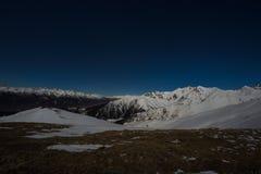 Vista stellata di notte del cielo sulle alpi Catena montuosa ricoperta neve nella luce della luna Immagini Stock Libere da Diritti