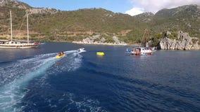 Vista stupefacente agli yacht che navigano nel mare aperto al giorno soleggiato con la gente che nuota e che fa i watersports archivi video