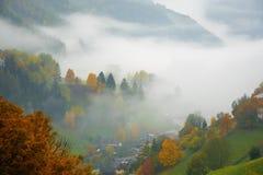 Vista stupefacente delle montagne in nebbia e della foresta variopinta di caduta nelle alpi della dolomia, Italia Fotografia Stock