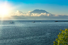 Vista su Bali dall'oceano, vulcano in nuvole Fotografia Stock