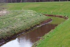 Vista su una vangata riempita di acqua con un'area dell'erba nel emsland Germania del rhede SME immagine stock