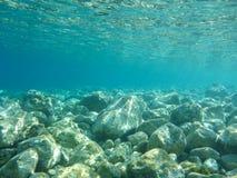 Vista SUBACQUEA dell'acqua della radura del turchese e dei ciottoli bianchi sparsi fuori dal fondale marino della baia di Antisam immagine stock libera da diritti