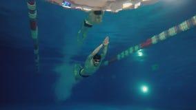 Vista subacuática al salto profesional hermoso del nadador en la piscina y el movimiento del crowl de la natación almacen de video