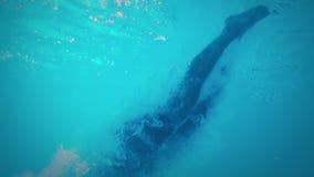 Vista subacuática del salto atlético del hombre en la piscina almacen de video