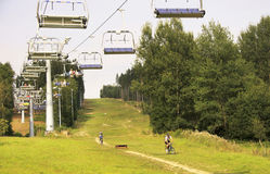 Vista sui ciclisti in mountain-bike e sullo ski-lift nel Lipno Immagine Stock