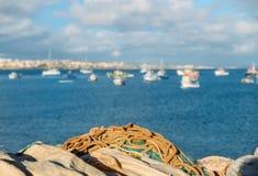 Vista sui precedenti, fuoco selettivo delle reti da pesca, del mare e del villaggio - catturato in Cascais, Portogallo Fotografie Stock Libere da Diritti