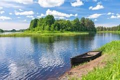 Vista sul fiume con l'isola e la barca di legno sovrapposte sulla riva fotografia stock