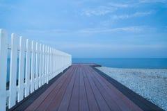 Vista sul mare con il molo di legno al crepuscolo fotografia stock libera da diritti