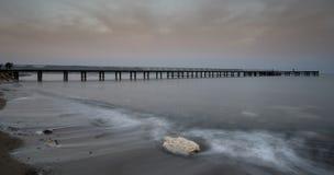 Vista sul mare con il molo durante il sunsrise nuvoloso drammatico Fotografia Stock