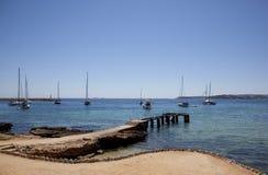 Vista sul mare con il pilastro e le vele Immagini Stock Libere da Diritti