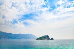 Vista sul mare con l'isola deserta nei cieli blu Paesaggio Mediterraneo Immagine Stock