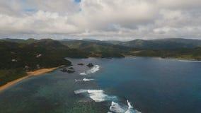 Vista sul mare con l'isola, la spiaggia, le rocce e le onde tropicali Catanduanes, Filippine video d archivio